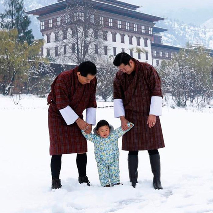 "Snow baby! The Dragon King celebrated the month of April by sharing a photo of himself enjoying ""the unexpected March snowfall"" with his son Prince Gyalsey and father Jigme Singye Wangchuck at the Lingkana Palace.