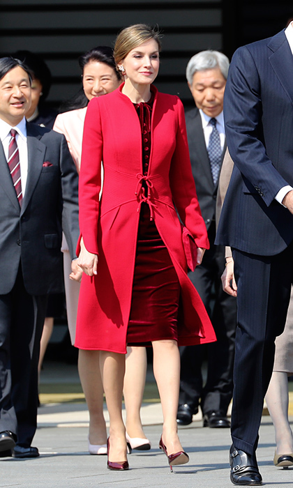 Queen Letizia of Spain mixed crimson hues at a ceremony in Tokyo – a bright red Felipe Varela coat worn with a burgundy velvet dress and matching heels. 