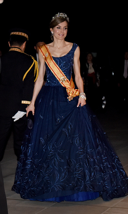King Felipe's wife embraced her inner Cinderella in this navy blue embroidered ballgown and gold sash to attend a state banquet at the Imperial Palace in Tokyo. 