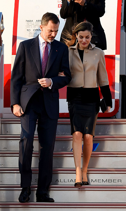 King Felipe VI of Spain and wife Queen Letizia arrived at Haneda Airport in Tokyo for their four-day state visit to Japan. Letizia wore a black dress under a camel and black colour-block coat.