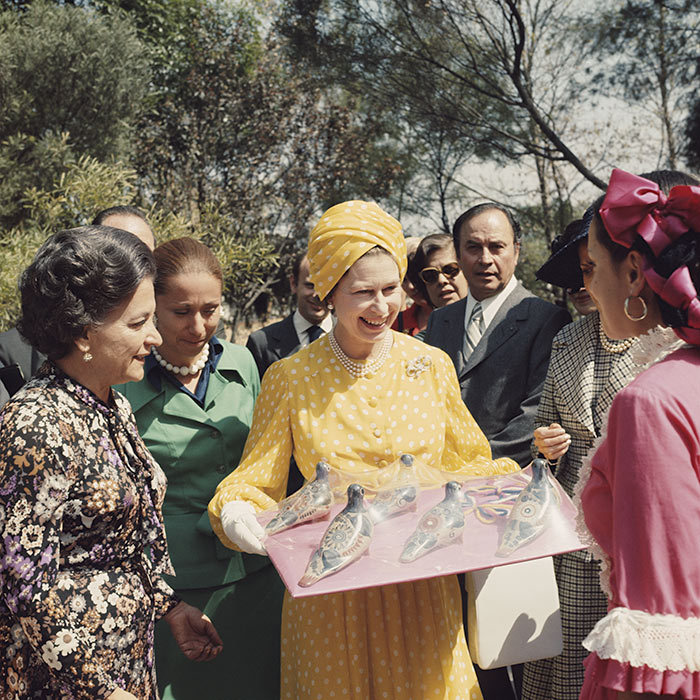<h3>A FLOCK OF HAND-MADE BIRDS</h3><p>Wearing a sunny yellow dress with white polka dots and a matching turban, the Queen proved herself a royal fashion icon during a state visit to Mexico in 1975. During her trip, the monarch met with local schoolchildren and was presented with a tray of handmade crafts. Her Majesty was the first British monarch to ever visit Mexico. She and Prince Philip returned for a second visit to the country in 1983. </p><p>Photo: © Getty Images</p>
