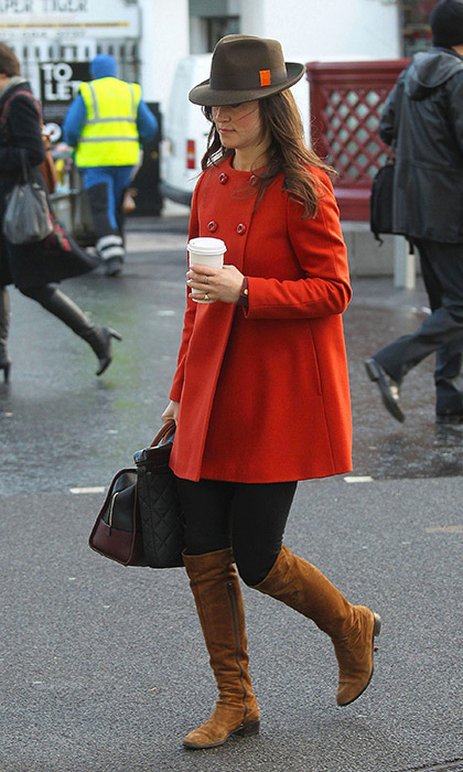 She perfected autumn street style in this orange coat, brown suede boots and fedora.