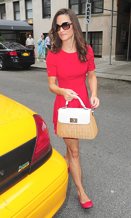 Pippa accessorized this cherry red ensemble with a pretty wicker handbag.