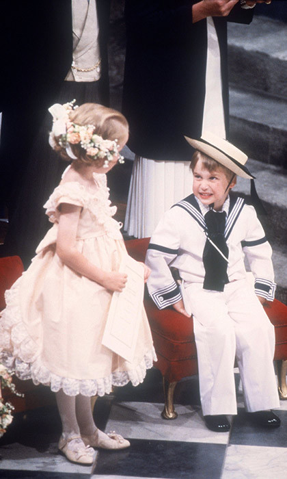 Prince William looked simply adorable in a sailor outfit, complete with a navy blue neckerchief and a matching straw hat, for the wedding of Prince Andrew and Sarah Ferguson in 1986. The little Prince pulled faces at a bridesmaid as they waited for the ceremony to start together.