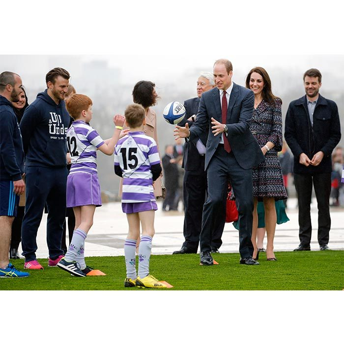 The parents of two are always up for sharing their love of sport with kids. During their official visit in Paris in 2017, Prince William tossed a ball around with young French rugby fans while Kate watched from the sidelines.