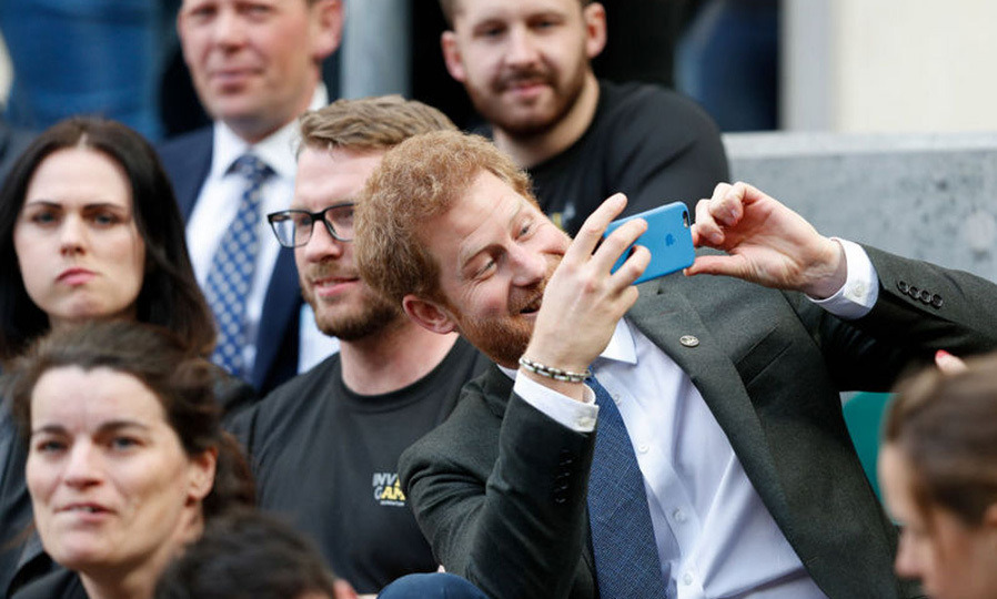 Prince Harry wanted to capture the moment on his iPhone during the annual Army Navy armed forces rugby match at Twickenham stadium on April 29.