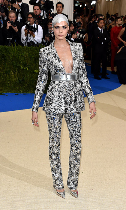 Cara Delevingne upped the ante again this year. The 24-year-old British model made a typically dramatic entrance in a futuristic metallic Chanel trouser suit featuring a plunging neckline - and to complete her stand-out look, the star had also painted her newly-shaved head silver.