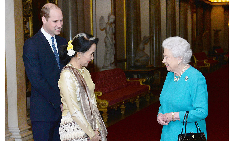 One day after his grandfather revealed plans to step down from his royal duties, Prince William helped his grandmother the Queen welcome Burmese politician Aung San Suu Kyi at Clarence House on May 5.