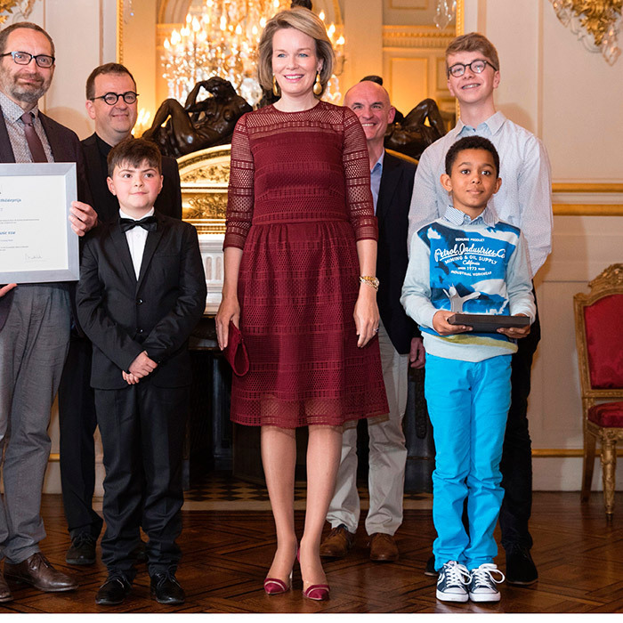 May 4: Belgium's Queen Mathilde wore a burgundy dress with lace overlay as she joined recipients of the Queen Mathilde Prize, left to right, Toon Beelaerts, Florian Lievens, Johannes Lievens and Kamiel Put at the Royal Palace in Brussels. 