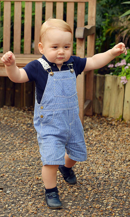 Dressed in blue dungarees for his first birthday photoshoot.