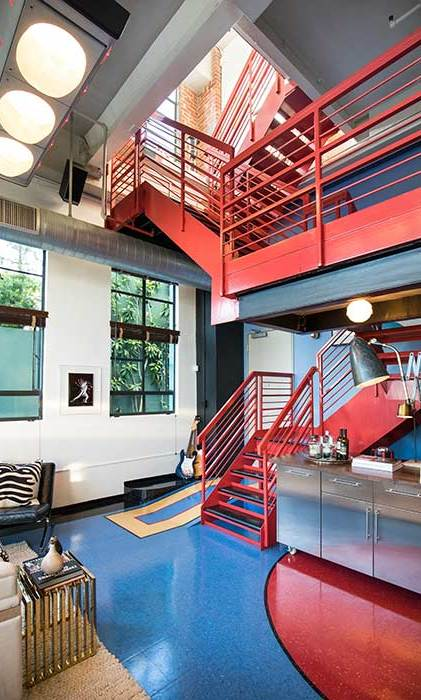 A focal piece of the penthouse is the winding red metal staircase that sits at the back of the lounge and kitchen and leads up to a mezzanine level, before reaching the property's two bedrooms and bathrooms. Glossy red and blue floor tiling runs throughout the ground floor of the penthouse and adds to the modern and colourful design.