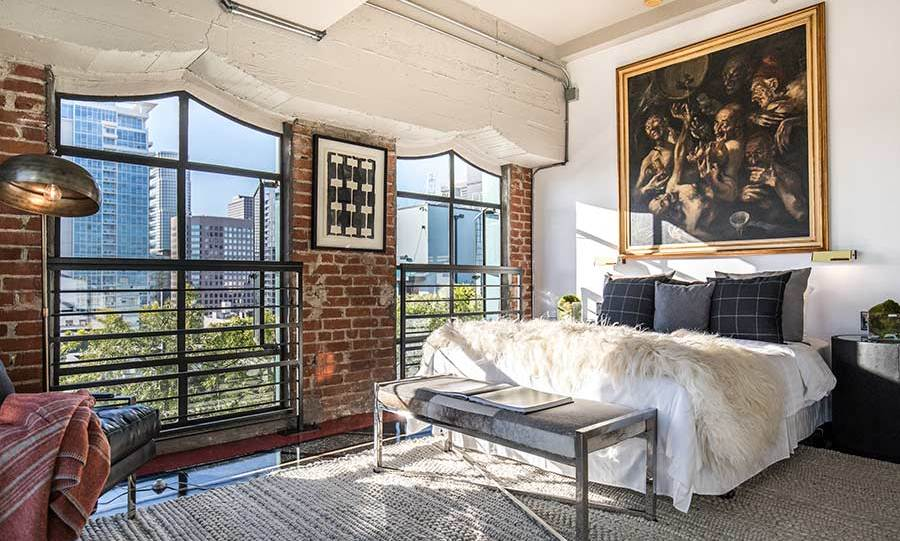 Arguably one of the highlights of the property is the master bedroom, which features huge floor-to-ceiling windows and has great views across the Los Angeles skyline. With exposed brickwork and pipes the room has a cool, loft-style vibe, and is currently decorated with a portrait from Johnny's personal art collection, which isn't available for sale.