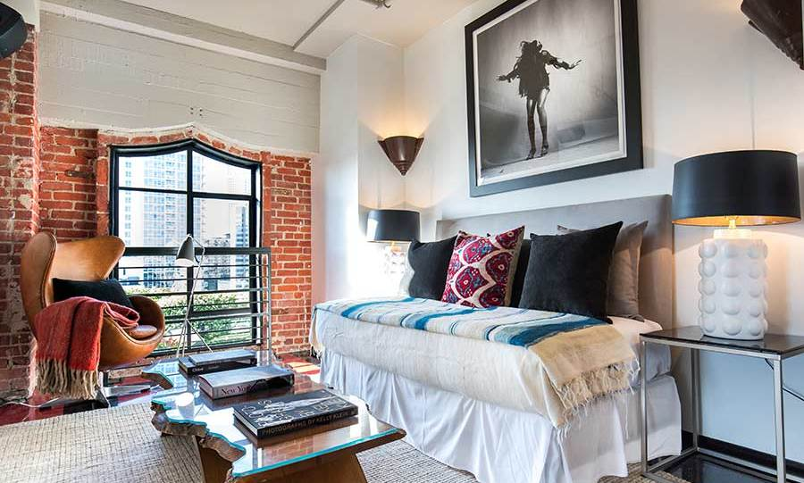 Johnny's penthouse has two bedrooms, including this smaller guest room that can also double up as a study or relaxation area with a sofa bed and comfy armchair located next to the window. Much like the rest of the property, this room has the same exposed brickwork and red tiled floor.