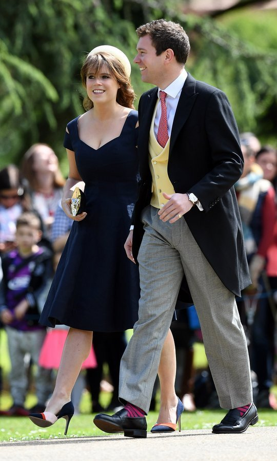 Princess Eugenie wore a pillbox hat and tailored dress with cutout shoulders as she and a guest arrived for Pippa and James' wedding. 