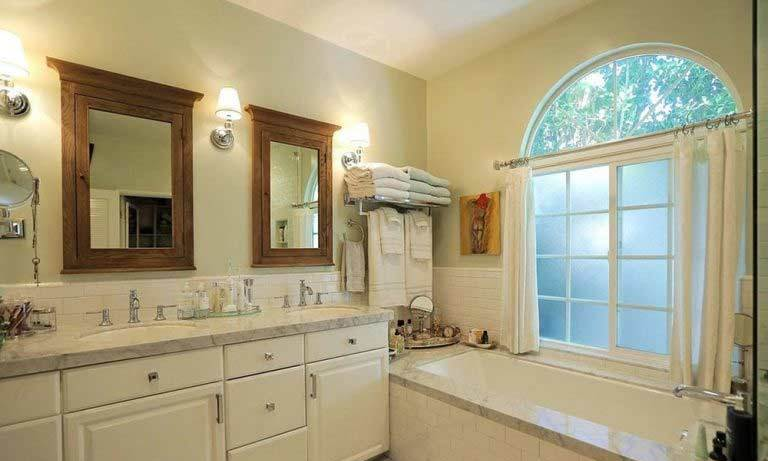 The bathrooms are fitted with marble surfaces and tiles, along with double vanity dressers. A large frosted window adds natural light and an airy feel to this bathroom, which is one of four across the main house and guest house.