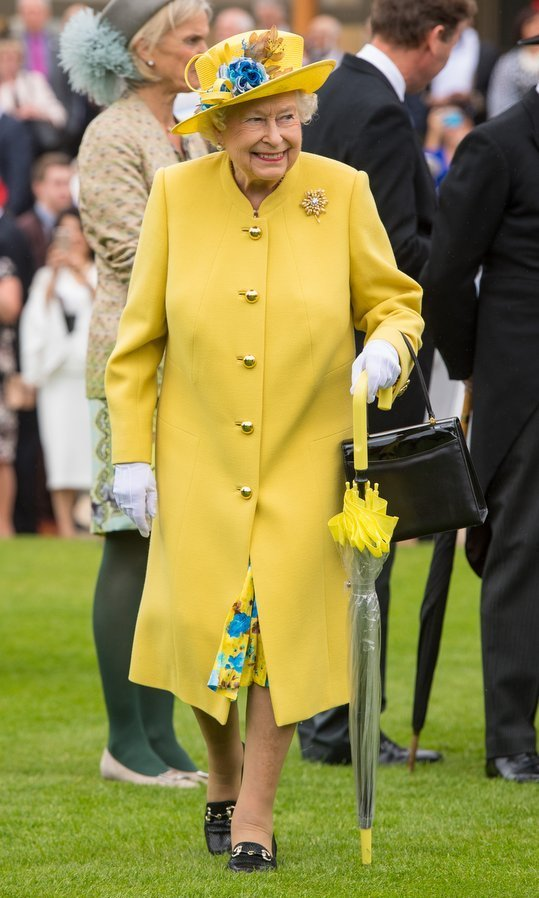 The Queen brought her own dose of sunshine in a canary yellow outfit – complete with matching umbrella! – as she hosted a garden party at Buckingham Palace.