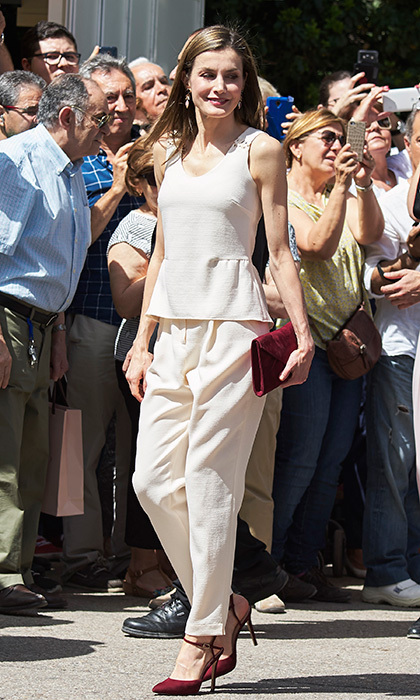 Queen Letizia added a burgundy clutch and heels to her summer-ready cream coloured outfit worn to the Madrid Book Fair in Retiro Park.