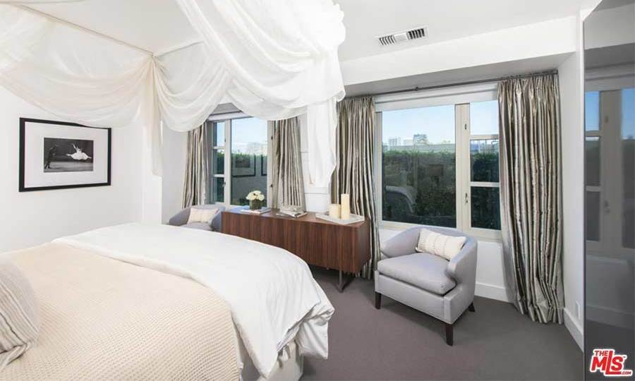 Kendall's apartment has two bedrooms including this suite which has double windows and great views out onto the LA neighbourhood of Westwood. The bedroom is decorated in a similar white and grey colour scheme to the rest of the home, and has a double bed with draped curtains hanging around the outside.