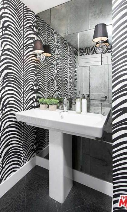 Another of the smaller bathrooms in Kendall's apartment has a unique monochrome design with black and white patterned wallpaper and a white fitted suite and black tiled flooring. This small bathroom leads onto the living room area, while there is a further en suite bathroom on Kendall's guest bedroom.