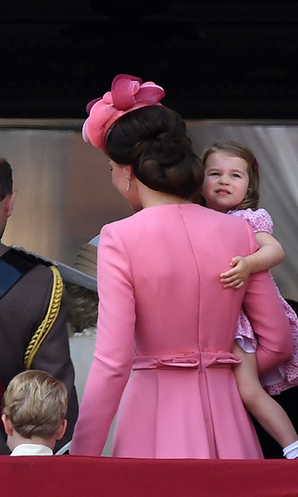Princess Charlotte takes a last look at the Trooping the Colour celebrations as she is carried back into Buckingham Palace by mum Kate, with brother Prince George at her side.