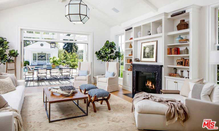 A large living room area has sliding doors that lead directly out to the garden and pool area, which has a dining table and cabana for relaxing outdoors. With white walls and soft neutral furnishings, this room has a light and airy feel, but also has a built in fireplace that will be ideal for cooler evenings.