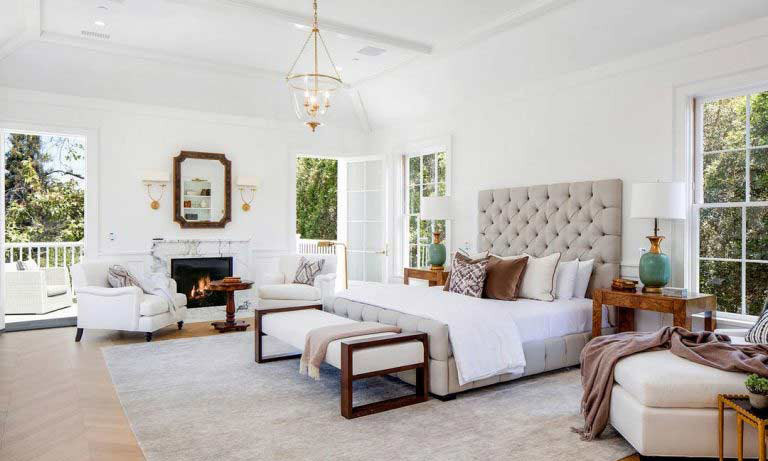 There are six bedrooms in the luxurious property, including this master suite that has a king size bed, plus room for two armchairs, a chaise longue and traditional fireplace. The spacious room overlooks the garden and swimming pool, and also has its own private balcony with a separate seating area.