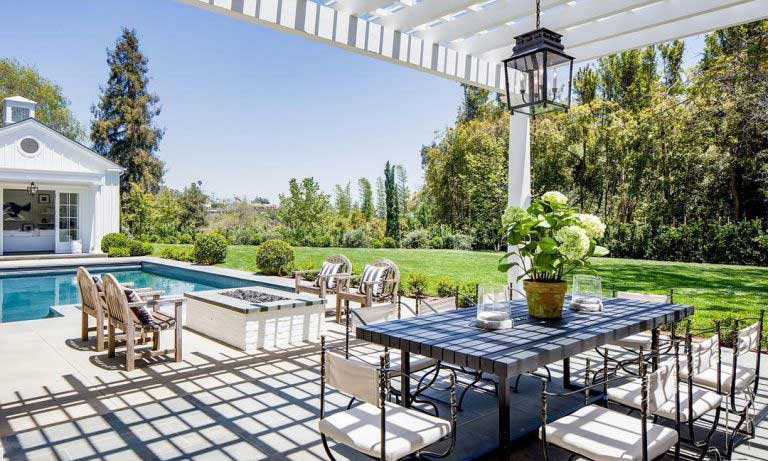 The residents can take advantage of the Californian weather in this stunning back garden, where there is a swimming pool area, cabana, comfortable seating and a dining table that is sheltered under a terrace, as well as a perfectly manicured lawn.