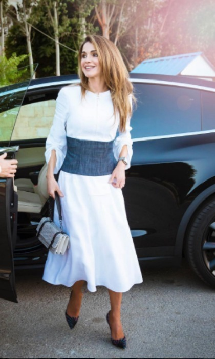 Queen Rania was on trend in an all-white dress that featured a denim corset for her visit with participants from the Teacher Education Professional Diploma and Advance Instructional Leadership programs in Jordan.