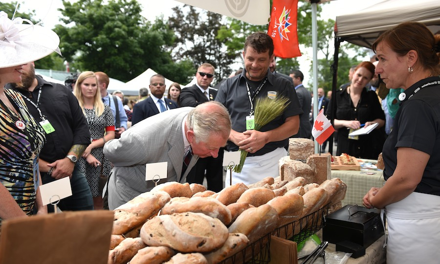 The future king takes a closer look at some freshly baked bread. The couple made sure to stop at every vendor for a lively chat about their offerings. 