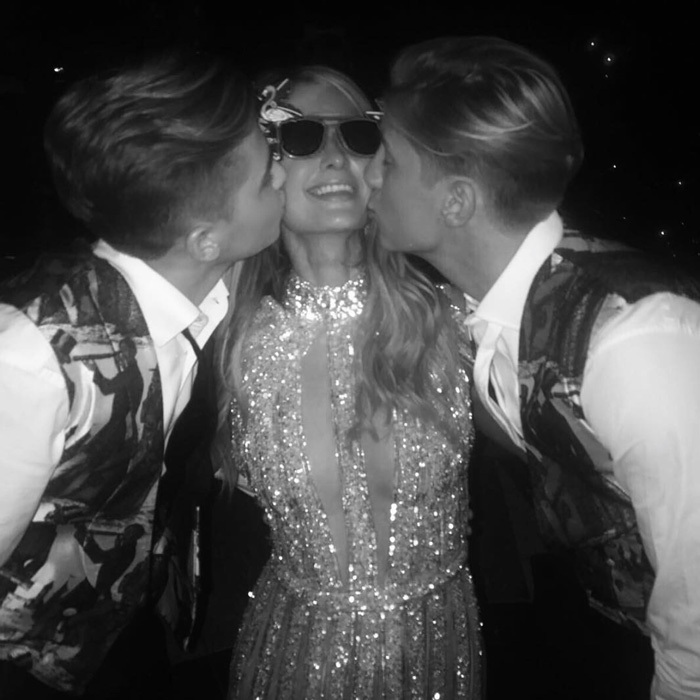 Olympia's younger brothers, Alexios (right) and Achileas (left), planted a kiss on guest Paris Hilton.
