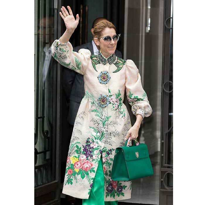 Celine celebrated Canada Day in Paris wearing a stunning Gucci embroidered satin coat, white stilettos, green pants and a matching green handbag.