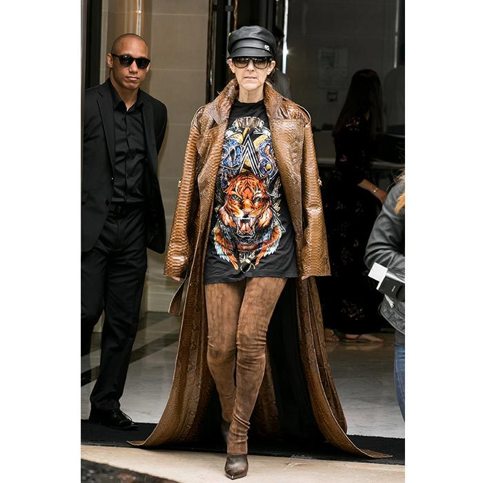 Celine made a bold fashion statement in a tiger-printed graphic tee, an over-sized snakeskin Balmain coat, thigh-high brown suede boots and a black leather hat while leaving the Royal Monceau Hotel in Paris on June 29. 