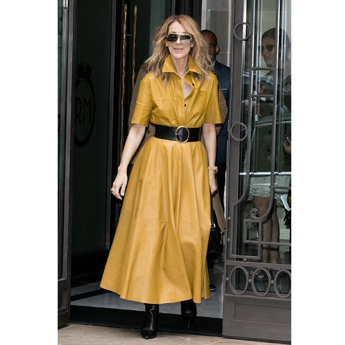 Celine stepped out in a mustard coloured leather dress paired with mirrored sunglasses, a wide black belt and stilettos on July 3 in Paris.