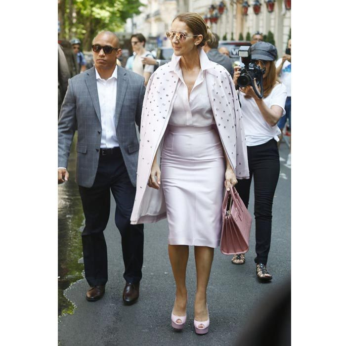 Celine strutted down the streets of Paris in a pale pink blouse, tight-fitting skirt and bejewelled coat by Dice Kayek with matching pink Casadei pumps and a Saint Laurent tote on June 20.