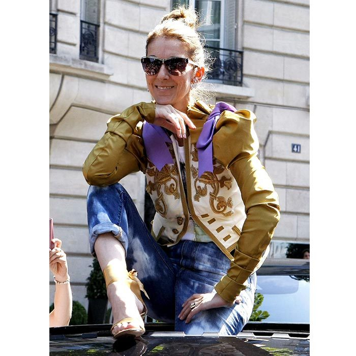 Celine struck a pose for fans on top of her car in Paris wearing a Dsquared2 military style gold blazer, acid washed jeans and Gianvito Rossi gold coloured heels on July 8.