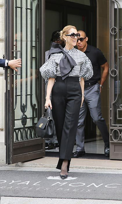 The Canadian icon is always on her fashion game! Celine walked out of her Paris hotel on July 5 in a black and white checkered Dice Kayek shirt and tailored high-waisted black pants by Céline, which she paired with a piece from her own handbag collection.