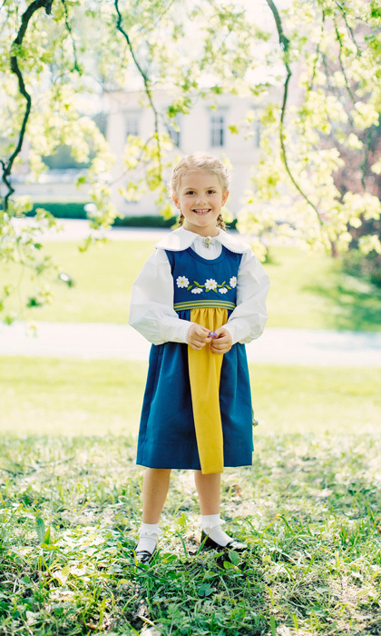 To mark Sweden's National Day, Princess Estelle smiled big in her traditional blue, yellow and white folk dress, while sweeping her golden locks up into braided pigtails. 
