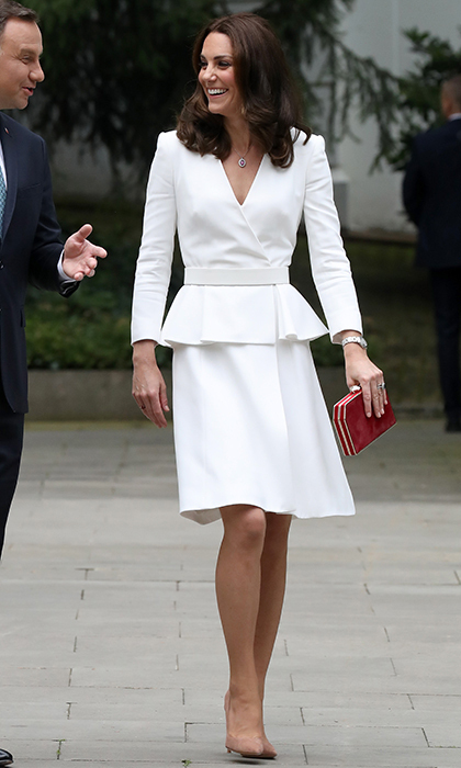 The Duchess of Cambridge wore a gorgeous white  Alexander McQueen dress, paired with nude pumps and a red clutch to kick off the royal tour of Poland and Germany on July 17.