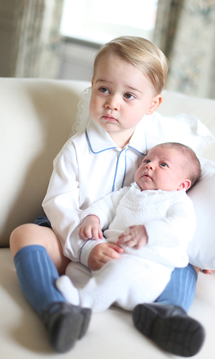 For Princess Charlotte's first official portraits, which were taken in Norfolk on 6 June 2015, proud big brother Prince George was seen gently kissing his sister's head.