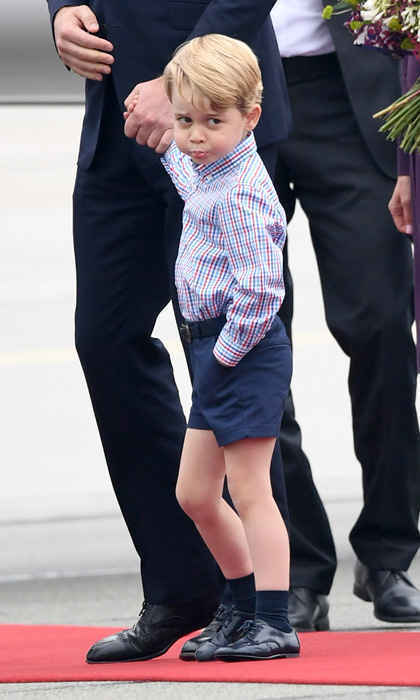 Prince George, sporting his signature shorts and socks, made a silly face as he held hands with his father, Prince William upon arrival to Warsaw, Poland on July 17, 2017.