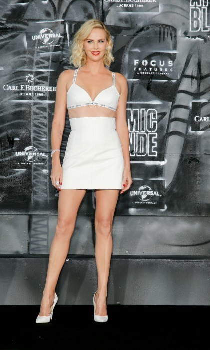Charlize Theron showed off her legs and abs in an all-white ensemble by Dior at the premiere of Atomic Blonde in Berlin, Germany on July 17.