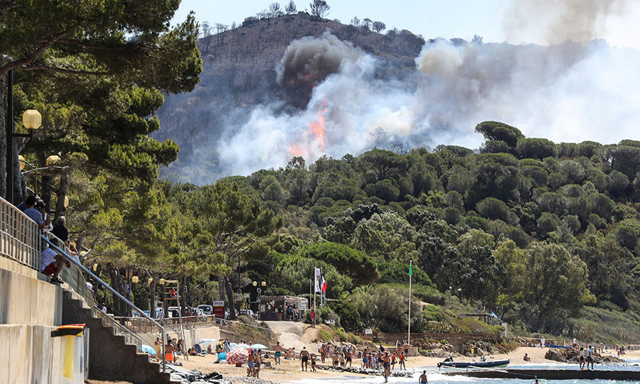 People enjoy the beach as a fire burns a forest by the sea in La Croix-Valmer, near Saint-Tropez, southern France on July 25, 2017. Firefighters battle blazes that have consumed swathes of land in southeastern France for a second day, with one inferno out of control near the chic resort of Saint-Tropez, emergency services say.