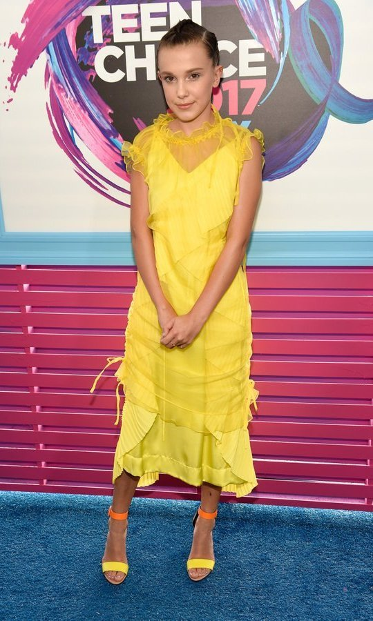 <em>Stranger Things</em> star Millie Bobby Brown continued her style streak at the awards show in this bright yellow dress by Kenzo, worn with Pierre Hardy shoes.