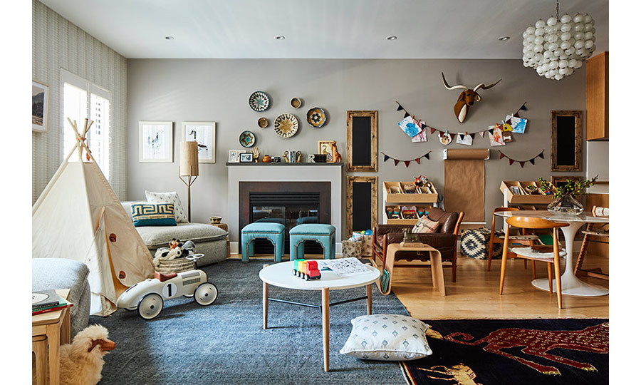 The living room is bursting with kitschy pieces – everything from the layered rugs to the decorative plates which adorn the walls alongside the strings of bunting, and the huge bauble light! Rockwell makes his stamp too with a big toy car reminiscent of Herbie, a kid's tent and a plush toy deer head.