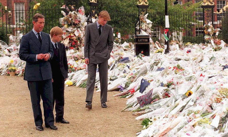 Prince Charles and sons Princes William and Harry take in the sea of floral tributes to their mother, Diana, Princess of Wales, at Kensington Palace, her former London residence in 1997.
