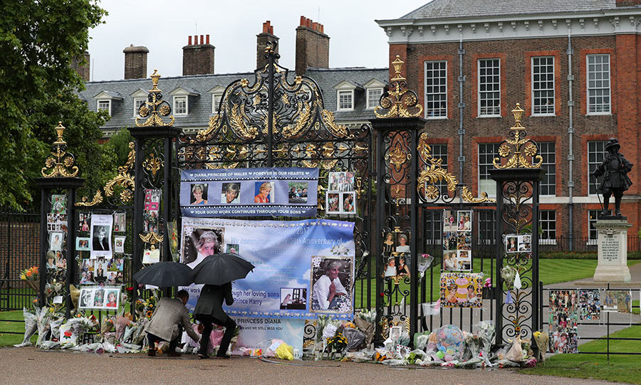 Prince William, Duke of Cambridge and Prince Harry look upon flowers, photos and other souvenirs left as a tribute to Princess Diana near The Sunken Garden at Kensington Palace.