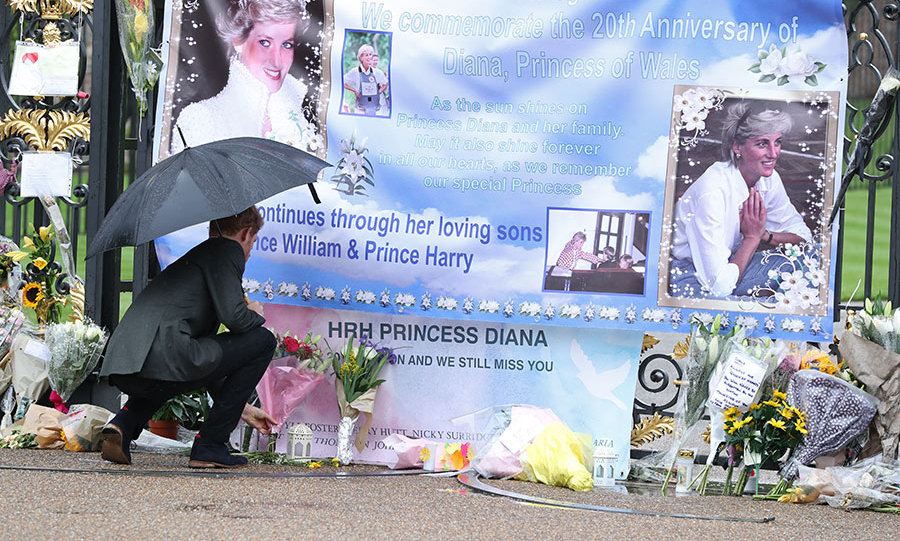Prince Harry lays flowers from fans left as a tribute to Princess Diana near The Sunken Garden at Kensington Palace.
