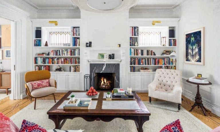 The middle parlour room on the ground floor features leaded stain glass windows and built-in bookshelves that surround a traditional wood burning fireplace. The perfect spot to relax, the room is furnished with two armchairs and a sofa, which is covered in a colourful throw and cushions.