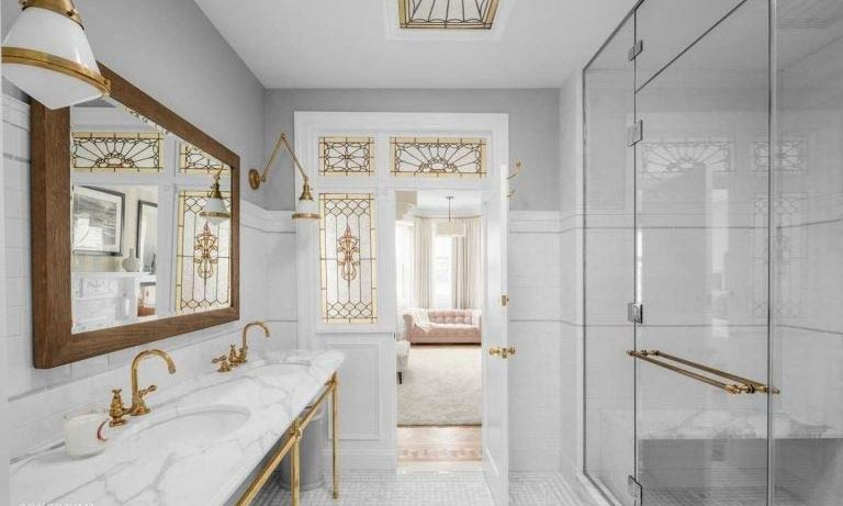 The master bathroom is pristinely decorated and gives a nod to the home's history, with light wells and a stained glass skylight adding unique finishing touches. It is one of three-and-a-half bathrooms in the townhouse, and features a walk-in shower cubicle, toilet plus a double vanity, with marble worktops and gold taps.