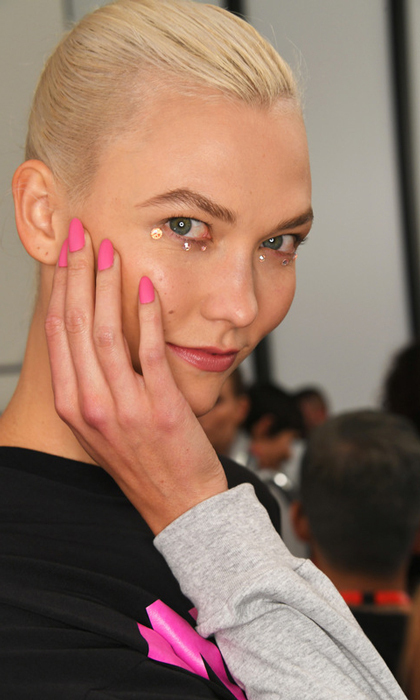 Karlie Kloss showed off her manicure by CND and her eye jewels backstage at the Jeremy Scott show.